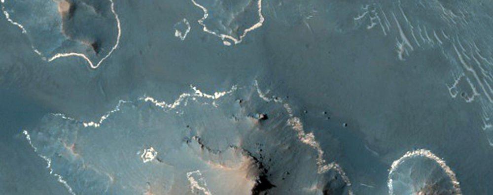 """Noctis Labyrinthus daki açık renkli kaya. """"Beyaz çizgiler tepelerin ve platoların etrafındaki malzeme tabakasını gösteriyor'' diyor McEwen. """"Diğer bir düşünce ise bu tabakanın geçmişte oluşan volkanik küllerin örtüsü olduğudur''"""