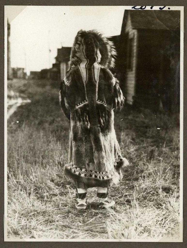 Araştırmacılar insanların kendilerini sıcak tutmak için porsuk ve diğer hayvanların kürklerini kullanma konusunda daha iyi olduklarına inanıyor. Bu fotoğrafta, bir eskimo kadınının ren geyiği ve porsuk kürklerinden oluşan bir parka giyerken görüyoruz. Fotoğraf Grönland'da 1921 yılında çekilmiş.